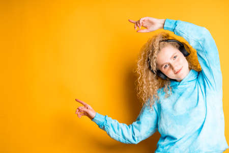 A young girl with curly hair and headphones points to the side. Place for inscriptions
