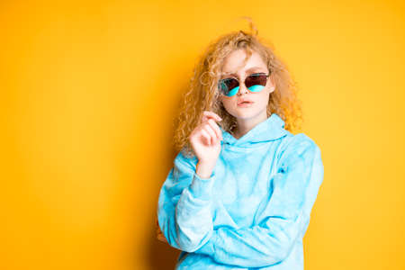 Charming woman with curly blonde hair in a blue sweater with glasses pulls back a lock of hair
