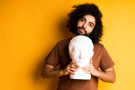 Handsome Egyptian with a beard standing on a yellow background and holding a head sculpture tilting his head to the side Foto de archivo