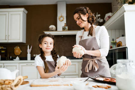 Mom in an apron teaches her little daughter how to sculpt from raw dough, shaping baking blanks with her hands
