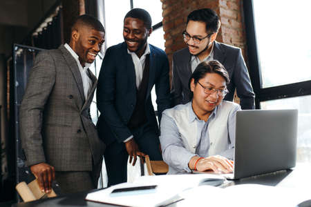 Cheerful african american and korean businessmen are smiling at each other and looking at the computer standing on the table