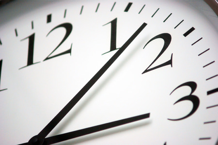 precisely: Closeup photo of a round black and white clock  Simple scale with minutes, hours and seconds
