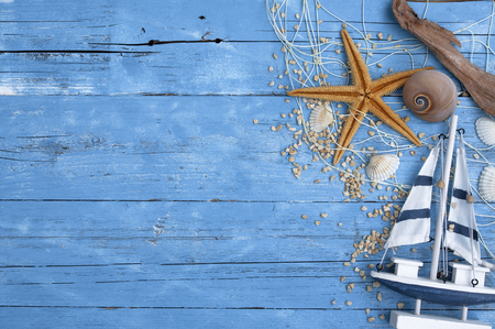 Maritime decoration on blue wooden background with wooden ship, starfish, shells, driftwood and fishing net