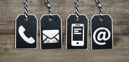 Black tags on natural wood with contact Banco de Imagens
