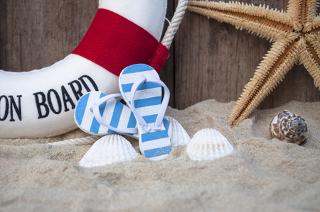 Maritime decoration with blue and white flip flops in the sand 스톡 콘텐츠
