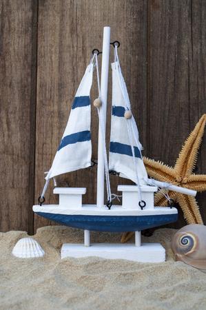Maritime decoration with shells, starfish, sailing ship, fishing net on blue drift wood Stok Fotoğraf