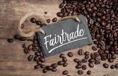 Chalkboard with coffee beans and a cup of coffee on natural brown wood Fair trade
