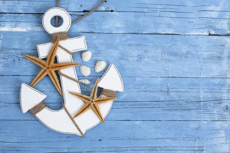 Maritime decoration with shells, starfish, sailing ship, fishing net on blue drift wood Foto de archivo