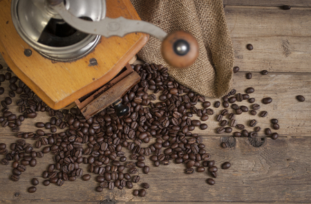 Chalkboard with coffee beans and cup of coffee on natural brown wood