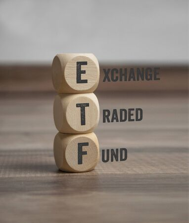 Cubes and dice with ETF and Funds on wooden background