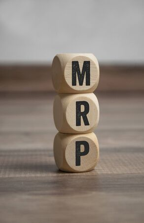 Cubes and dice with MRP Material Requirement Planning on wooden background