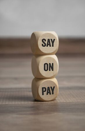 Tower made of cubes or dice with business term Say on pay on wooden background