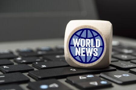 Cube and dice on laptop keyboard with world news