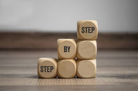 Cubes and dice with with term step by step on wooden background