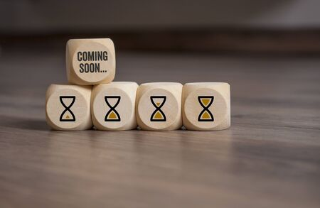 Cubes dice with hour glasses icon and coming soon on wooden background