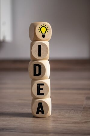 Cubes dice with lightbulb an pdca concept - plan do check act on wooden background