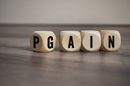 Cubes and dice with two words Pain and Gain on wooden background Stock Photo