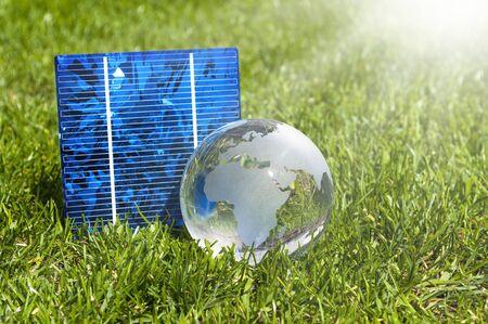 Células de energía solar con glas globe y casa en miniatura en pasto verde