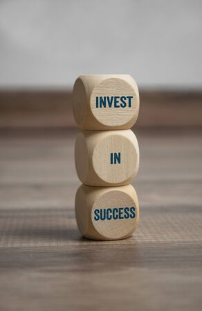 Tower made of cubes and dice showing the message invest in success on wooden background