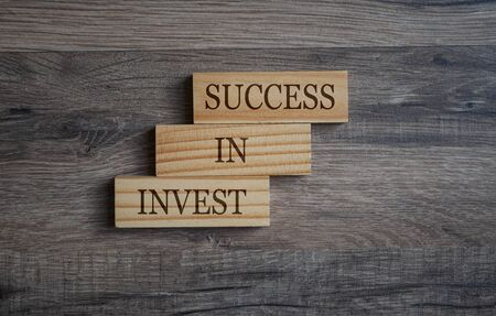 Wooden blocks with business message invest in success on wodden background