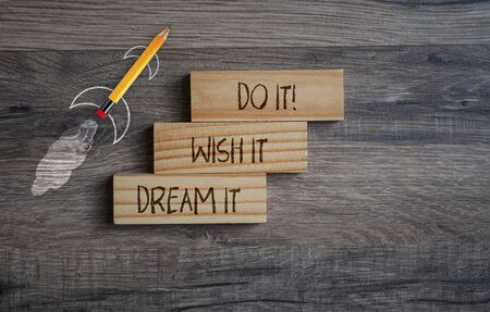Pencil rocket withg business message Dream it, Wish it, Do it on wooden background