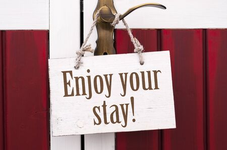 Golden door handle with wooden card board and with message Enjoy your stay Archivio Fotografico