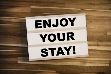 Lightbox or light box on a wooden tablet with message Enjoy your stay