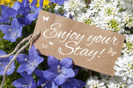 Paper card board with flowers and plants with message Enjoy your stay Archivio Fotografico