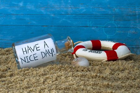 Maritime decoration with blue weathered wood and message in a bottle Have a nice day