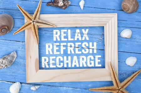 Blue weathered wood with marine or maritime decoration and message Reflex Refresh Recharge in a frame Stock fotó