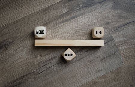 Cubes and dice with work life balance on wooden background Reklamní fotografie