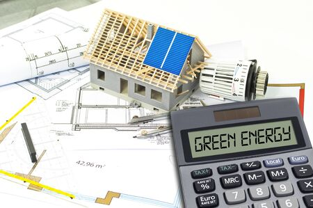 Solar energy cells on a blueprint or construction plan with calculator showing the word green energy