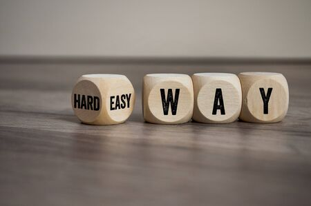 Cubes and dice with words hard way or easy way on wooden background