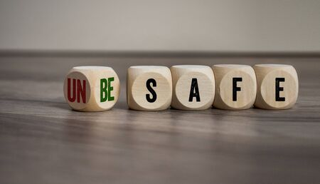 Cubes and dice with unsafe and be safe on wooden background
