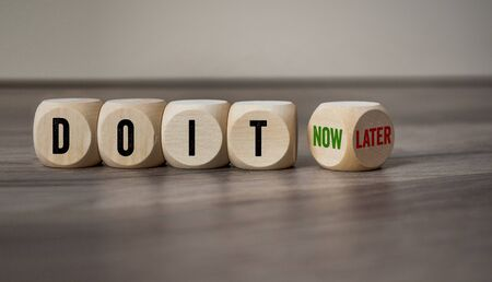 Cubes and dice with the words Do It now and later on wooden background