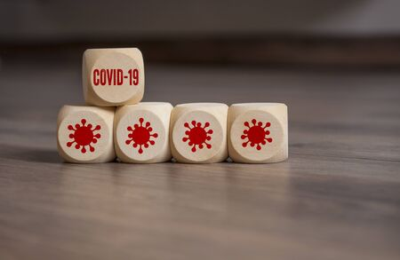 Cubes and dice with covid-19 corona virus on wooden background Stock Photo