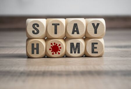 Cubes and dice with Stay Home and corona virus on wooden background