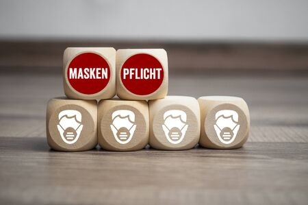 Cubes and dice with corona virus and the german words for face mask duty - maskenpflicht on wooden background