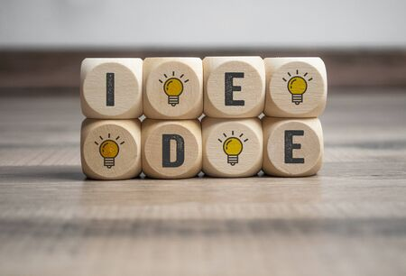 Cubes and dice with light bulb icon and idea on wooden