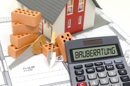 Calculator with the german words for house construction -Bau advice with clinker bricks and blueprint with miniature house Archivio Fotografico