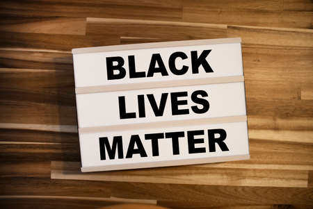 Light box or lightbox with message Black Lives Matter on a wooden table background