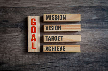 Wooden pieces with GOAL and mission, vision, target and achieve on wooden background