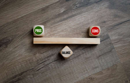 Cubes or dice with balance between pros and cons on a wooden background