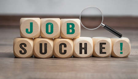 Cubes or dice with magnifier or magnifying glass and the german word for job search - job search