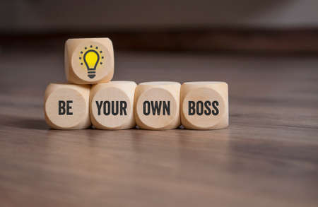 Cubes or dice with lightbulb and message Be your own boss on wooden background