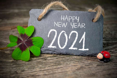 Wooden hang tag and slate with four leaf clover and sparklers with happy new year 2021 on wooden weathered background Archivio Fotografico