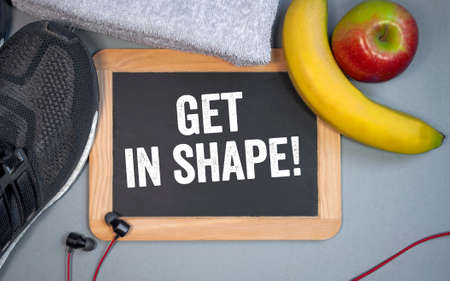 Chalkboard or blackboard with fitness equipment and message Get In Shape Archivio Fotografico
