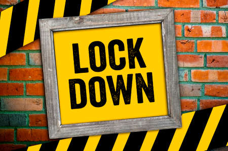 Yellow sign with message Lockdown in front of a clinker wall Archivio Fotografico