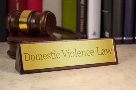 Golden Sign with gavel and Domestic Violence Law on a desk Archivio Fotografico