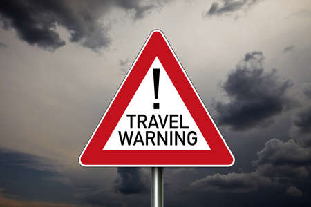 Traffic sign with covid-19 corona virus and travel warning with dark cloudy sky